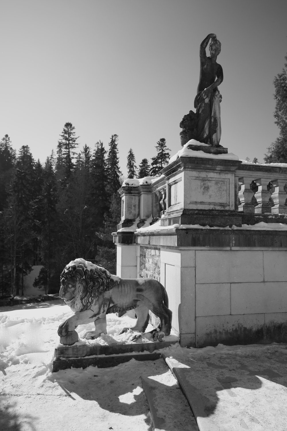 Garden statues - a lion and a greek lady, with snow piled high.