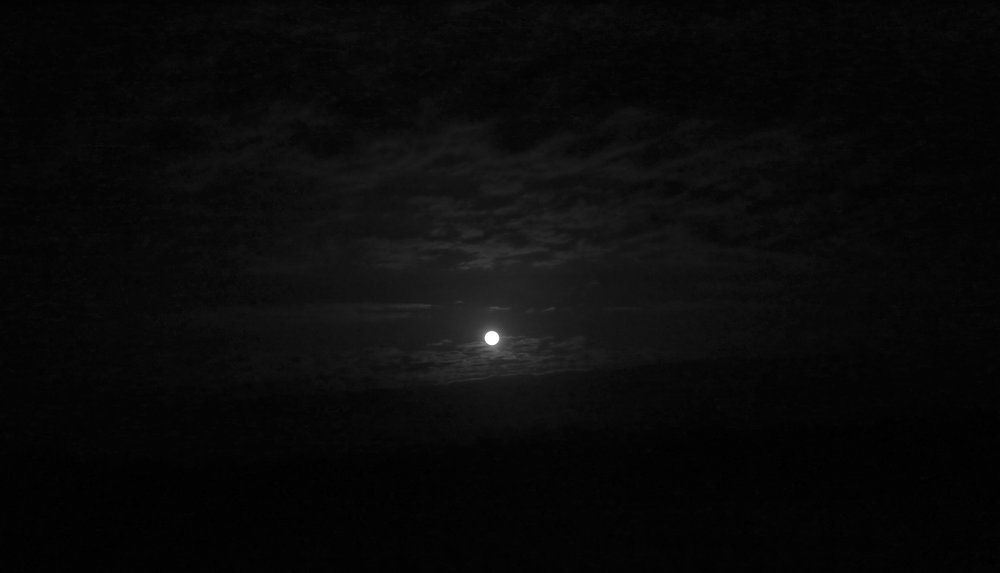 Full moon, with clouds, in black and white.