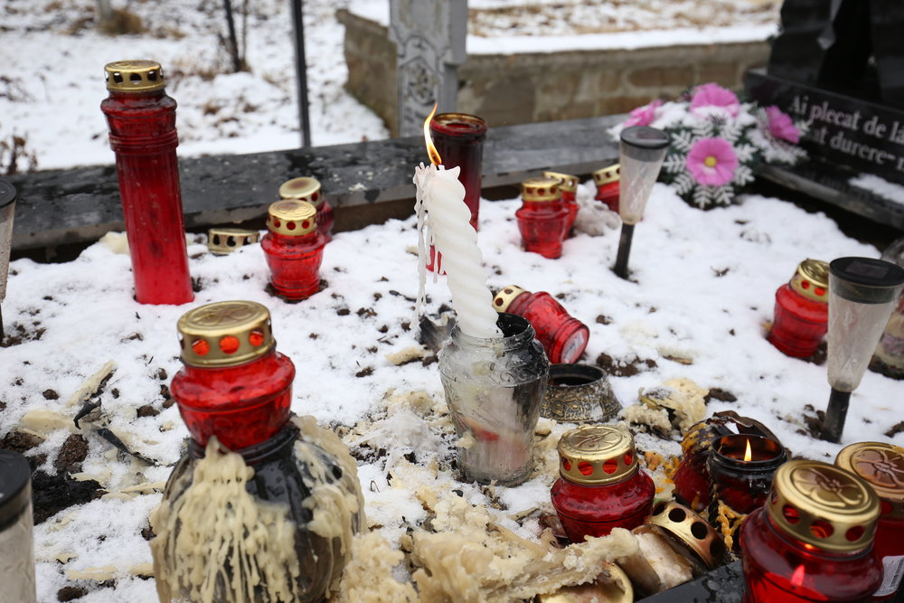 Red candles on a grave in a Romanian cemetery.