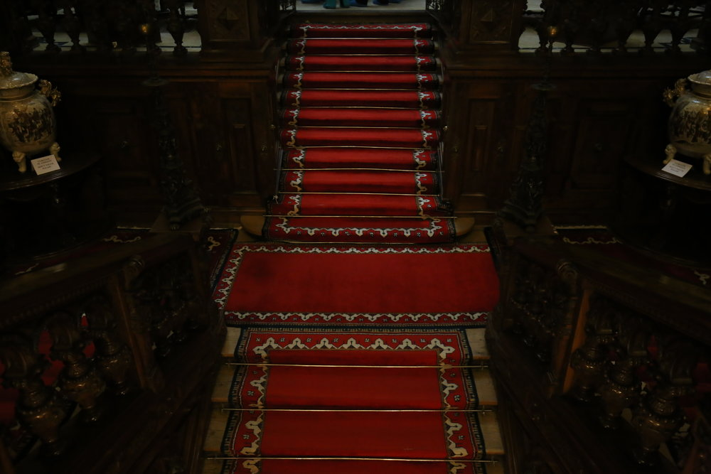 Old red carpets on endless stairs in Peles Castle, in Romania.