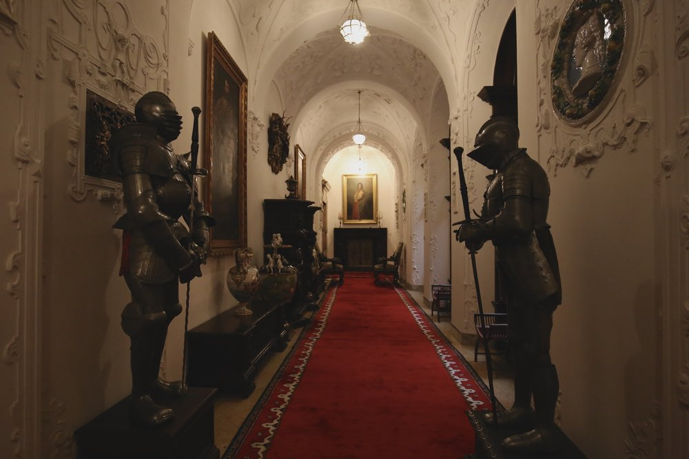 Suits of armour in a dark hallway at Peles Castle, Romania.