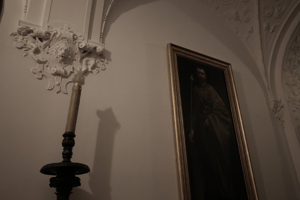 Candles and old portraits in a dark hallway of a castle.