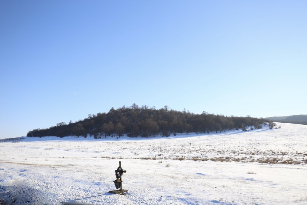 Cross by the roadside with a snow covered hill.