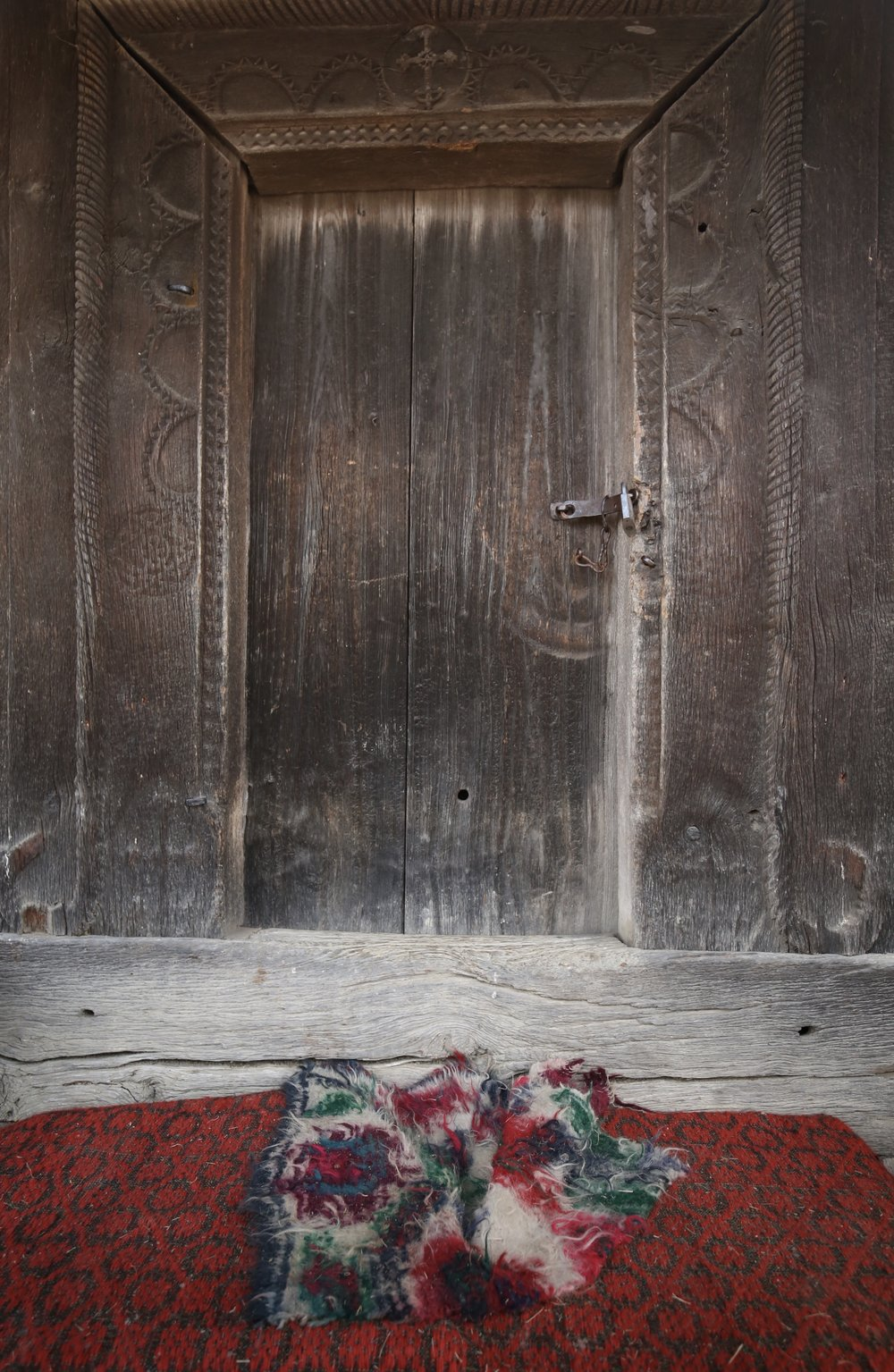 A red carpet in front of a small wooden door, Romania.