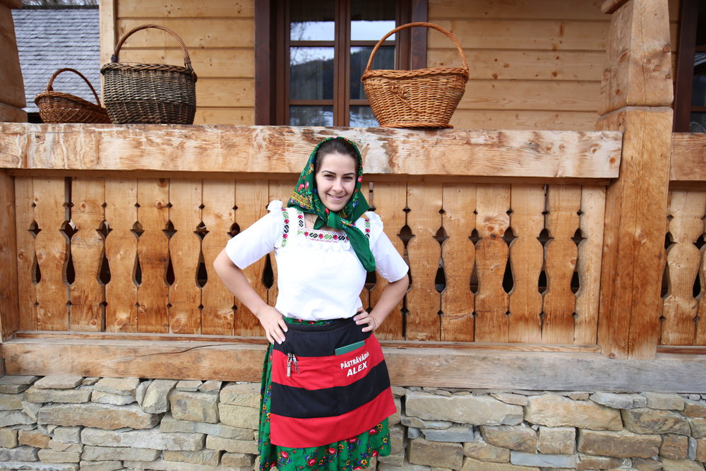 A young lady in traditional Romanian dress with a flower patterned skirt and headscarf.