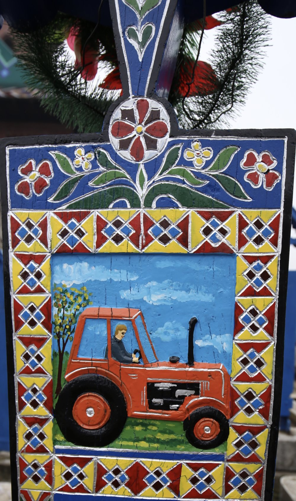 A grave marker in the Merry Cemetery - showing a bright painting of a tractor.