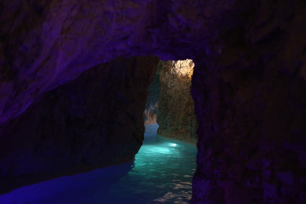 Purple cave walls and blue water.
