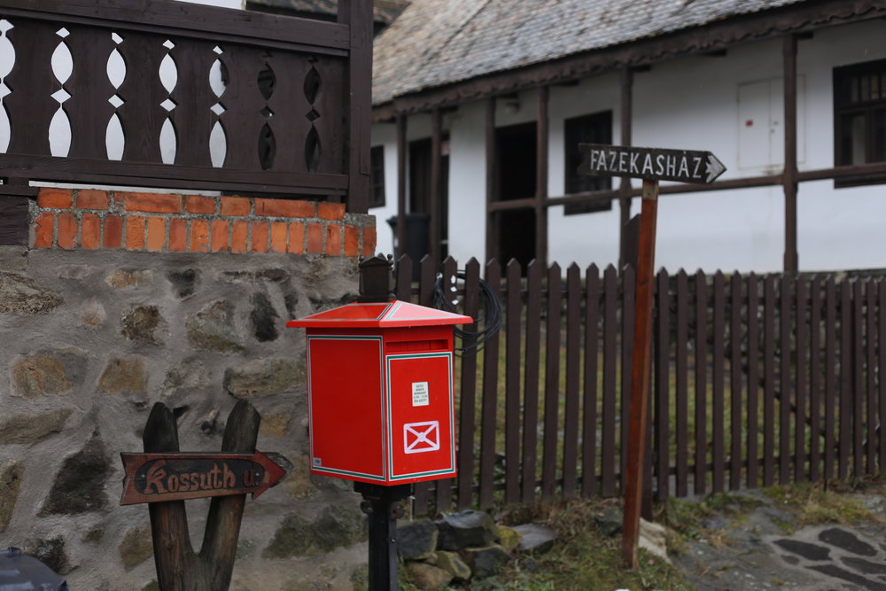 An old fashioned red post box in the UNESCO town of Holloko