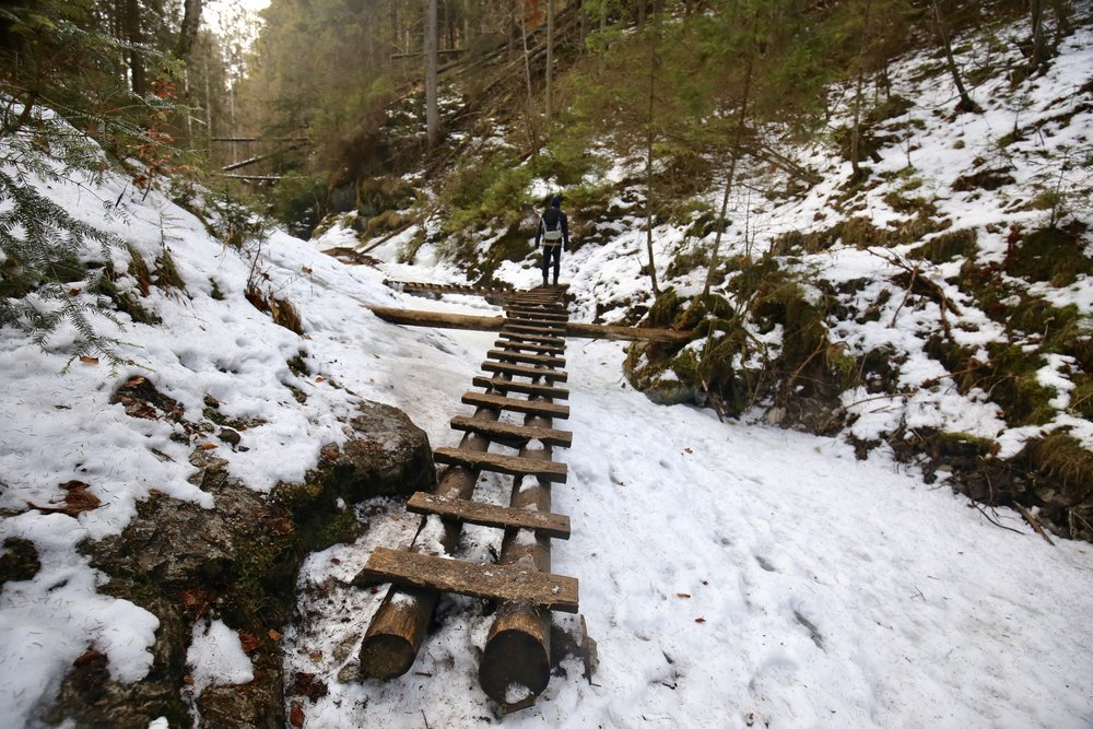 Wooden ladders over a frozen river at the Slovak Paradise National Park.