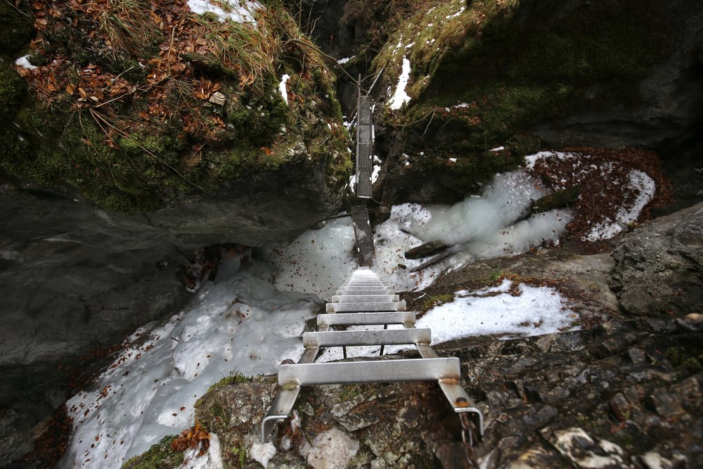 A steep drop - looking down a metal ladder at the icy valley below, hiking in Slovak Paradise Park in winter.