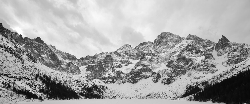 Lake Morskie Oko and the Tatras Mountain range, in winter snow, black and white photography.