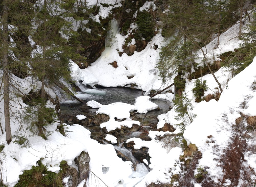 Waterfalls and blue pools in snow on the hike to Morskie Oko.