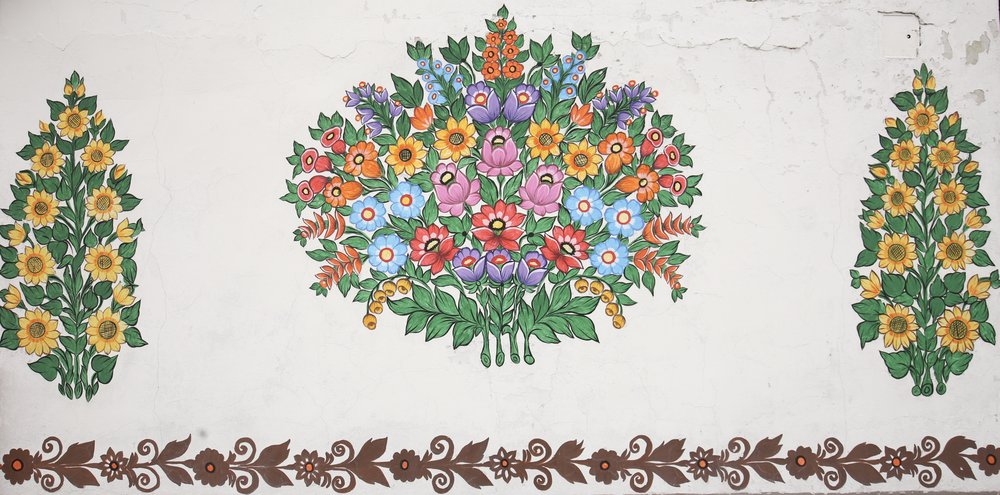 The flowers of Zalipie, Poland. A bouquet and sunflowers painted on a white wall.