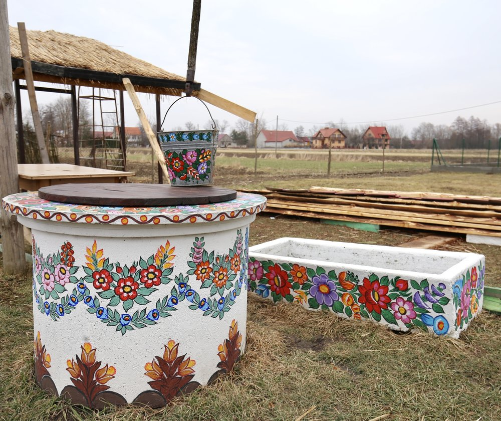 A bucket hanging over a well, painted with bright flowers, in Zalipie.