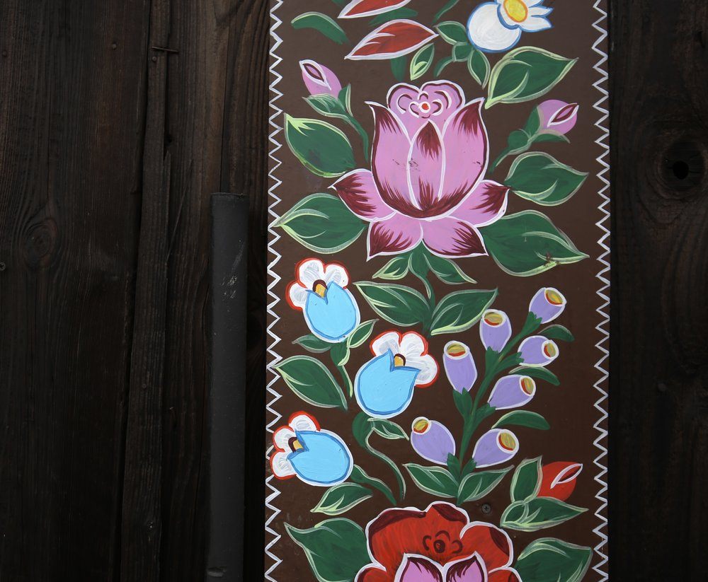Bright flower details painted on an old brown barn in Zalipie, Poland.