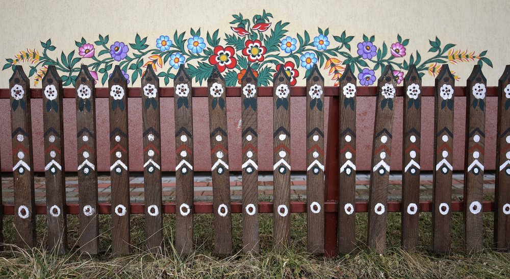 A little wooden fence and wall painted with colourful flower patterns in Zalipie, Poland.