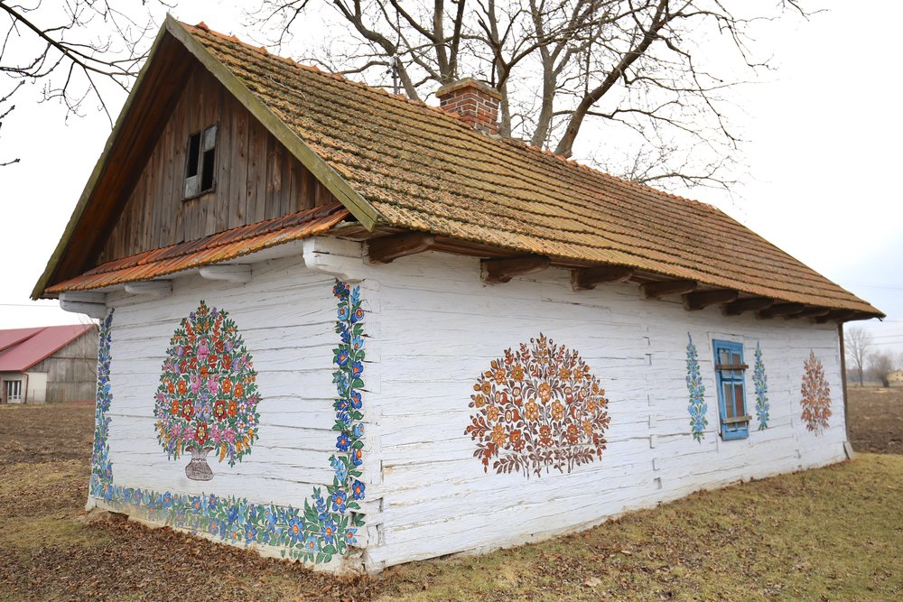 A charming little cottage with tiled roof and white walls painted with colourful wreaths of flowers, Zalipie, Poland.