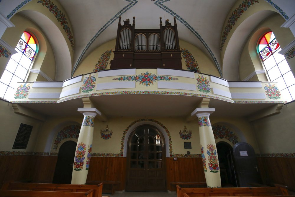 A church organ sits above the pews, on a painted balcony of bright flowers, Zalipie Church.