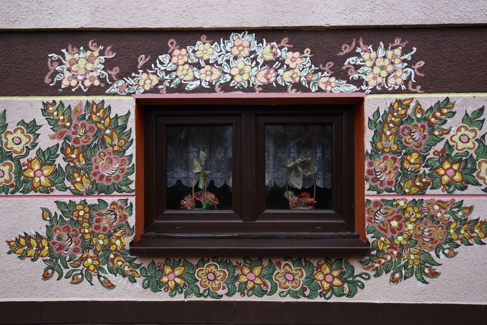Looking in at the window - brown and pink flower patterns on a small house in Zalipie.