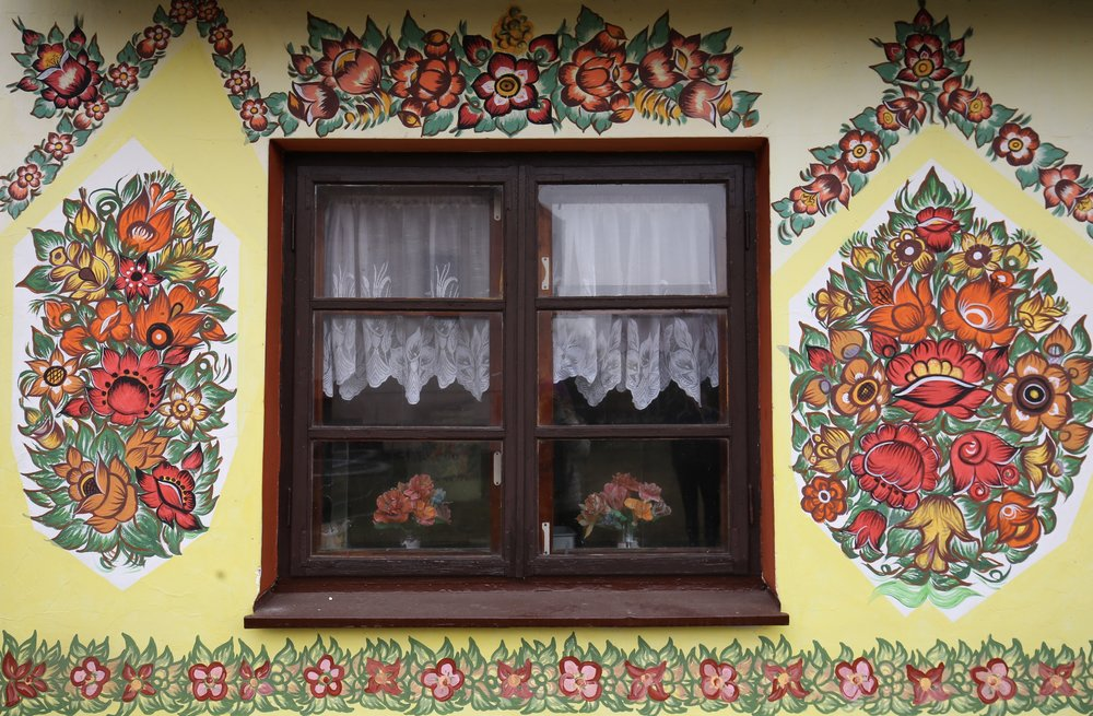 Brightly patterned walls on an old barn window in Zalipie - with orange and red flowers.