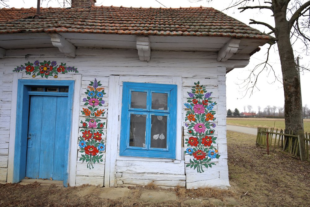 The sweetest little blue cottage door with painted flowers hung all about - in Zalipie, Poland.