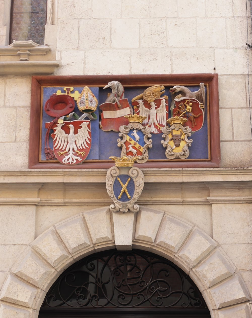 Sculpted and painted tympanum showing a coat of arms and an eagle.