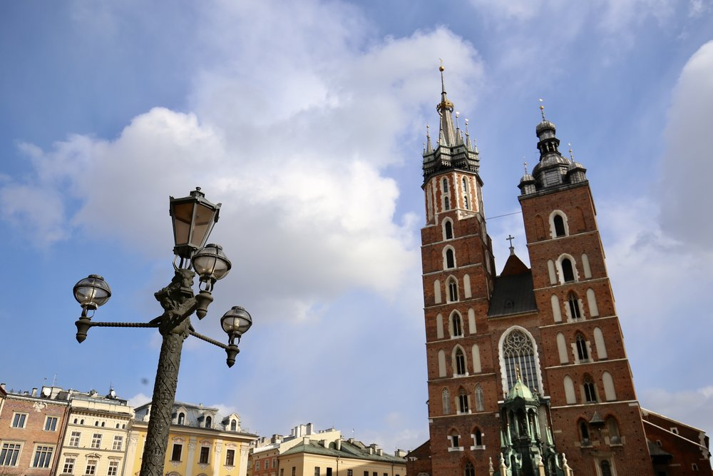 St Mary's Basilica in Krakow on a sunny day, with a lamp-post in front.