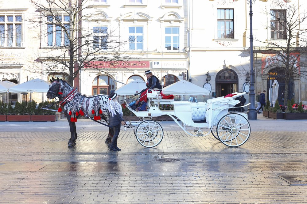 A fairytale-like horse drawn carriage in the cobbled streets of Krakow.