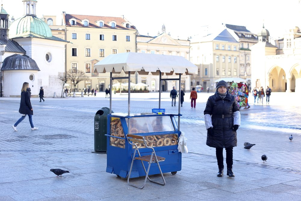 A pretzel seller by her stand in winter, with pigeons all around, Krakow.