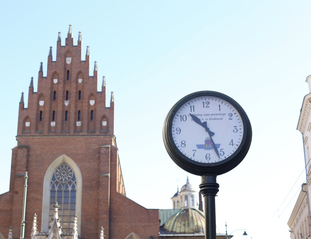 An old lamp-post style clock and a polish church, Krakow.