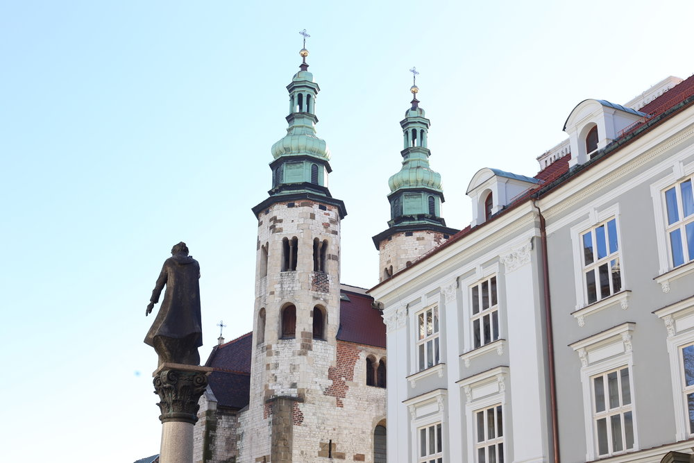 A statue in front of two church spires, on a winter's day in Krakow.