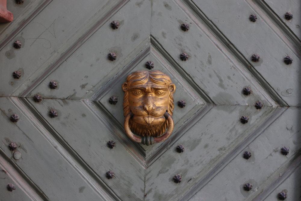A gold lion door knocker on an old studded door, in the streets of Krakow.