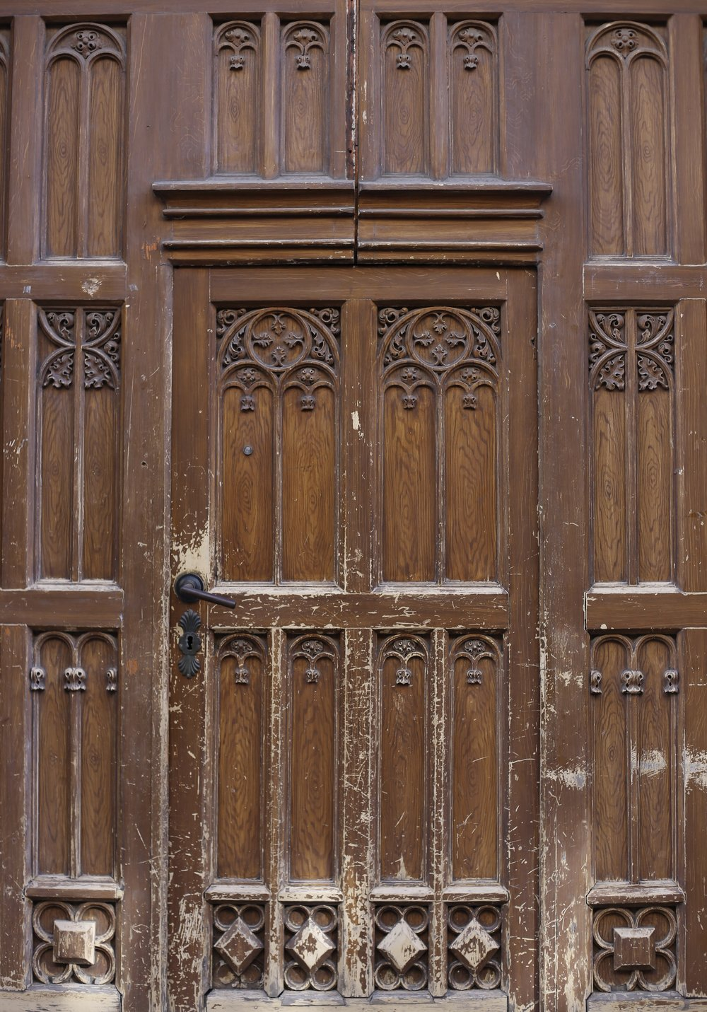 A battered wooden door with delicate detailing and carvings.