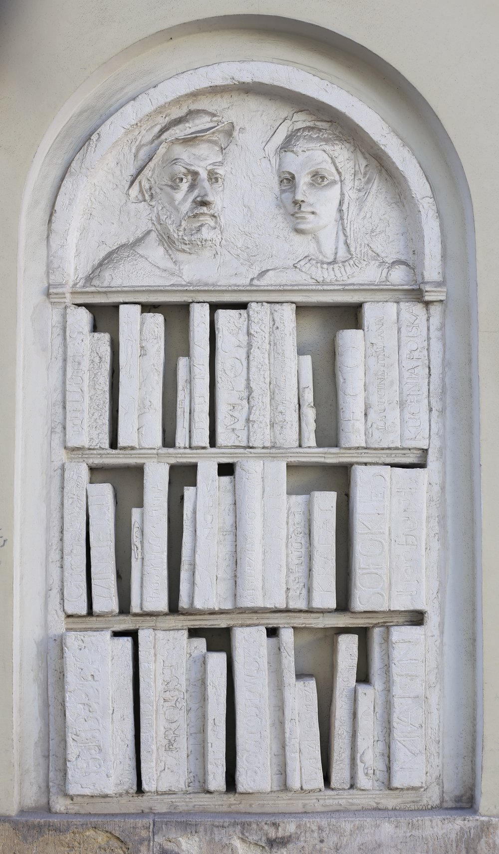 A stone bookcase watched over by two stone guardians, on a wall in Krakow.