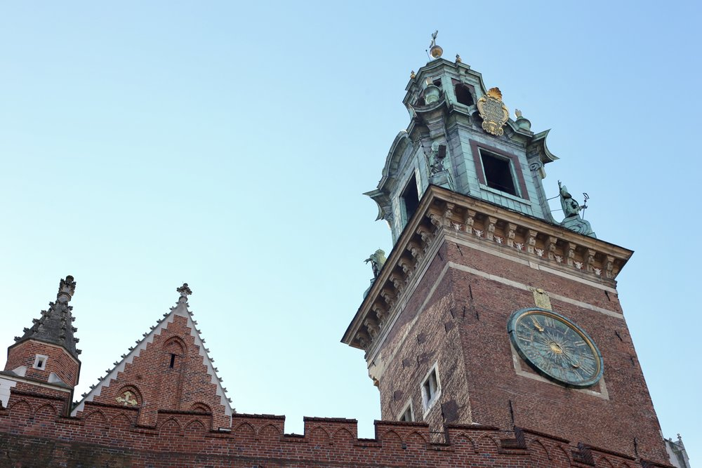 Wawel castle stone walls and turret details with a blue sky.