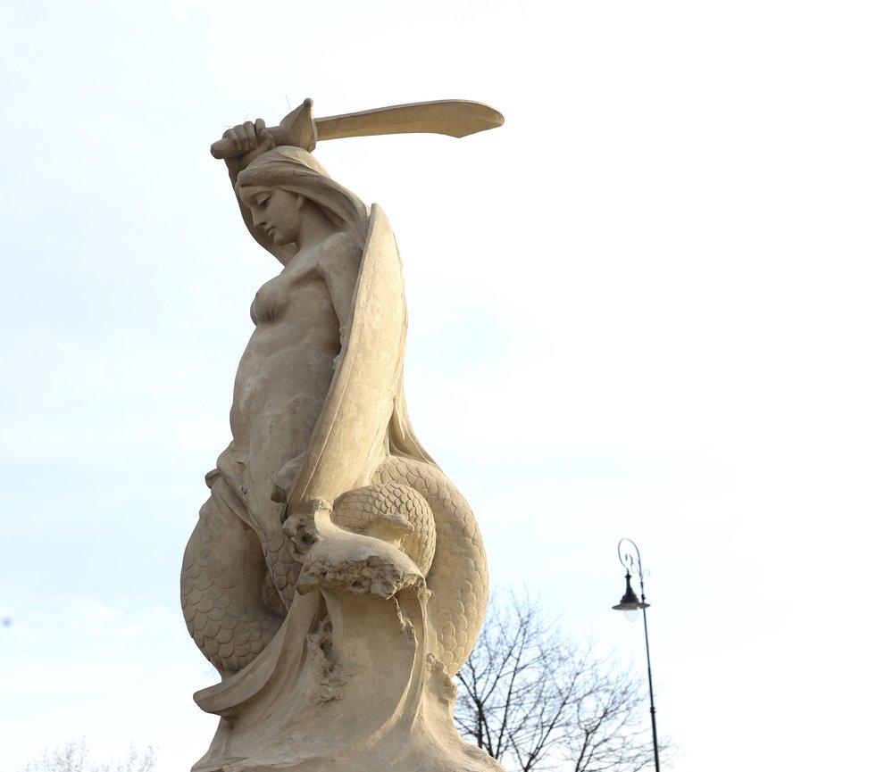 The Warsaw mermaid in white stone.