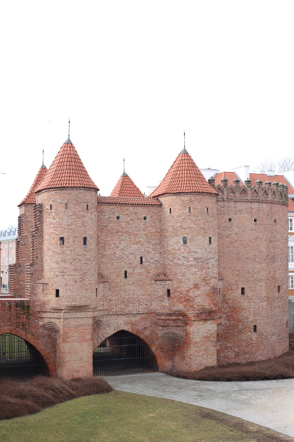 A small turreted castle-like town gate made of red brick, on the edges of Warsaw old town.