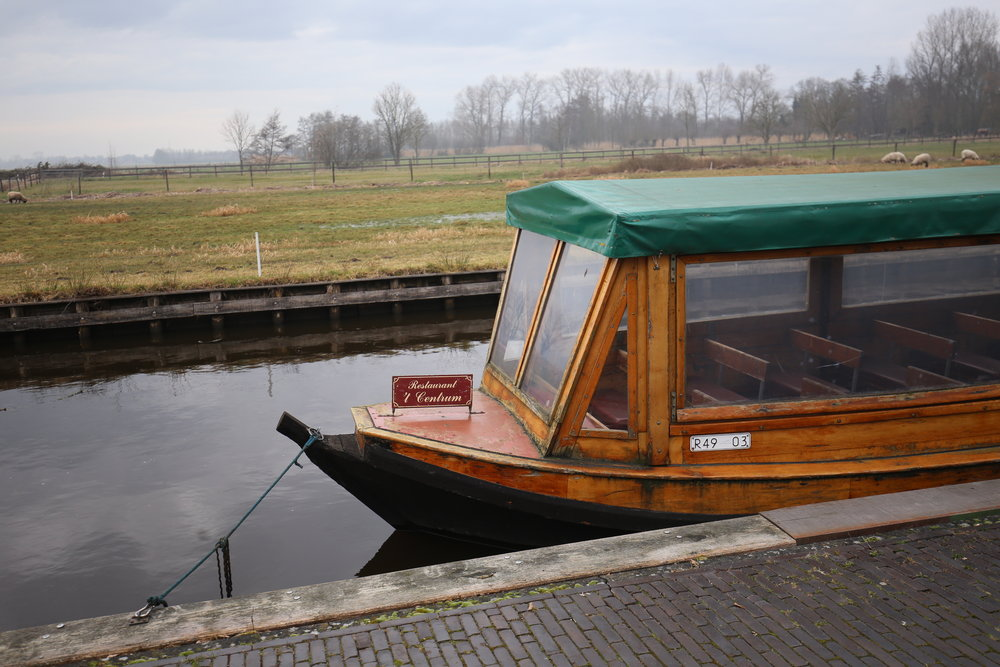 A wooden boat on the canals of Giethoorn.
