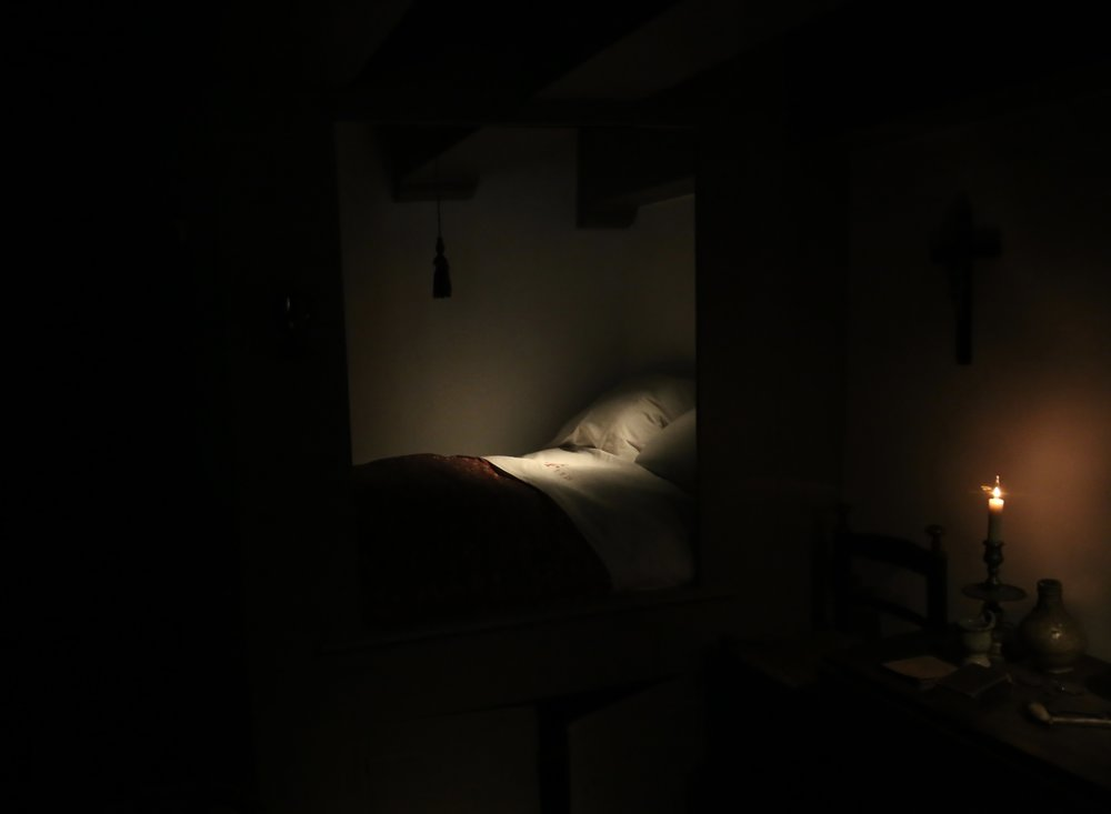 A 17th century box bed in the dark and light of a candle.