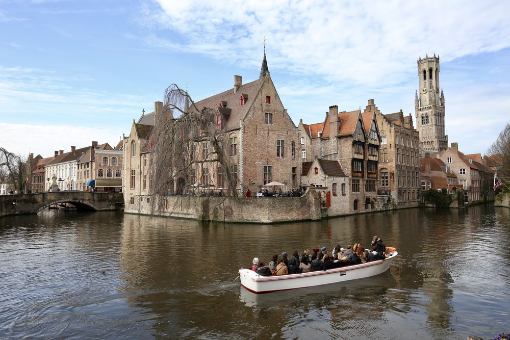 The old town of Bruges - a boat leaves off the dock of the canal, by medieval houses.