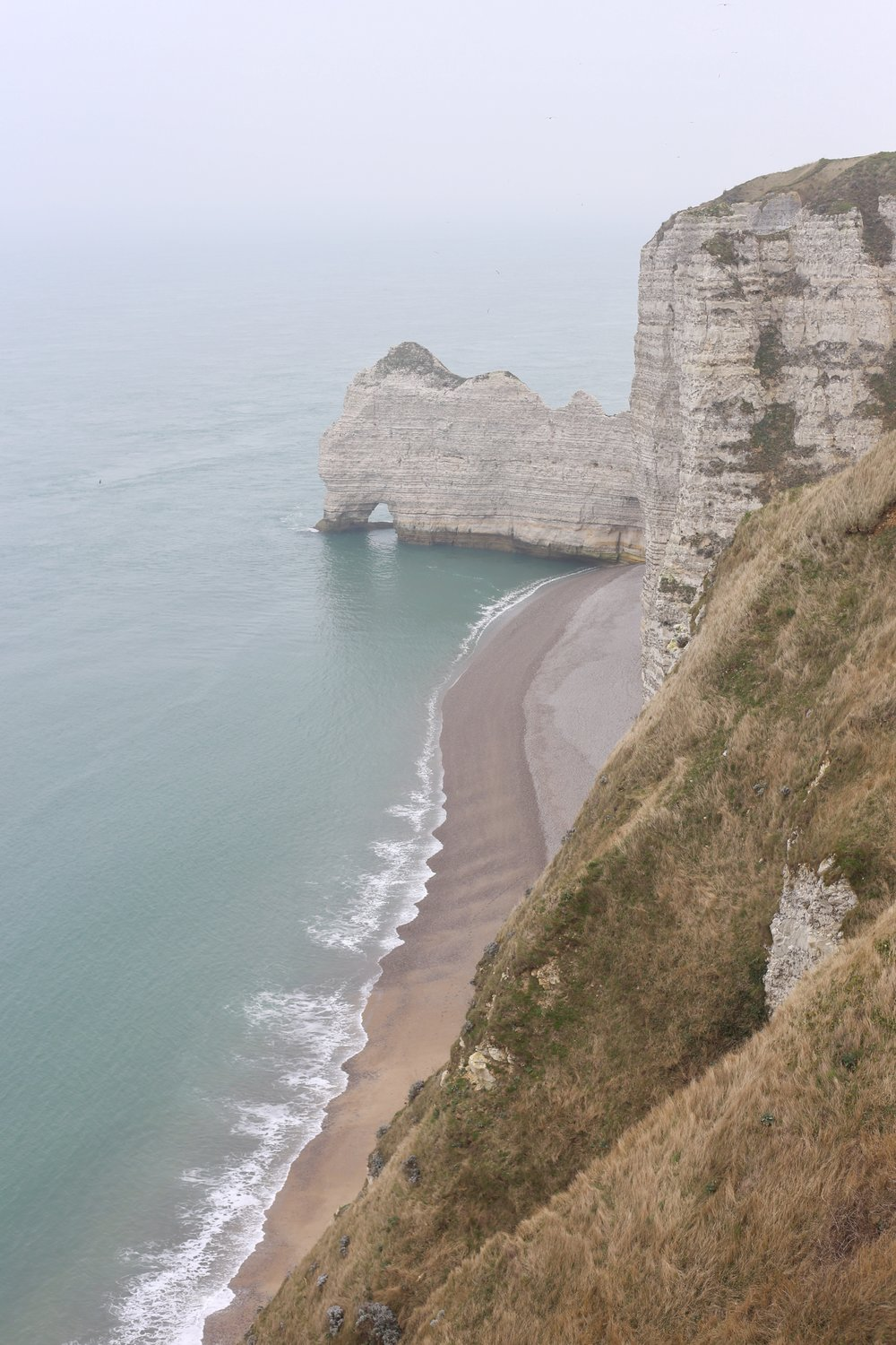 Falaises d'Étretat - the white cliffs of Etretat by the blue sea, France.