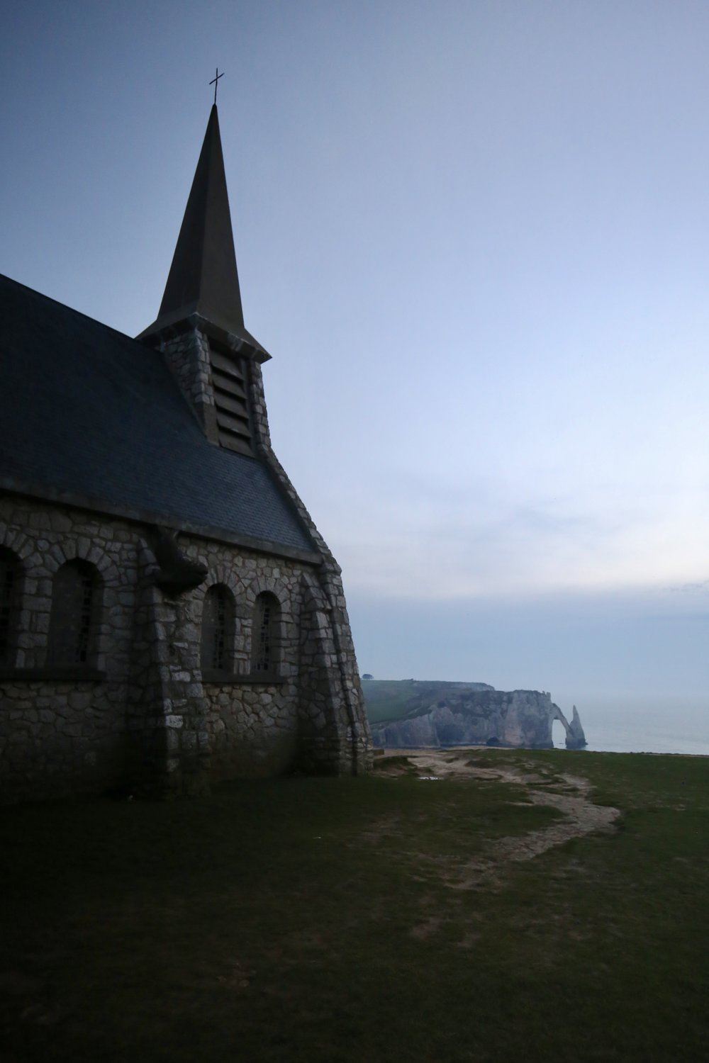 The church looking over the cliffs of Etretat at dusk.