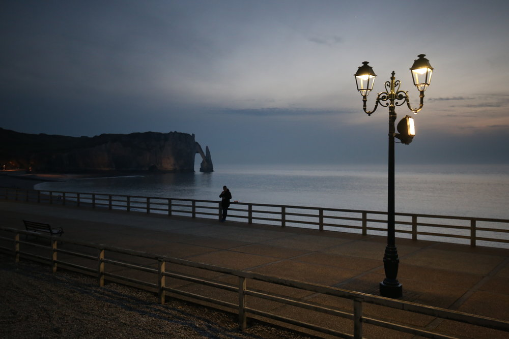 Lamp light by Etretat beach at dusk.