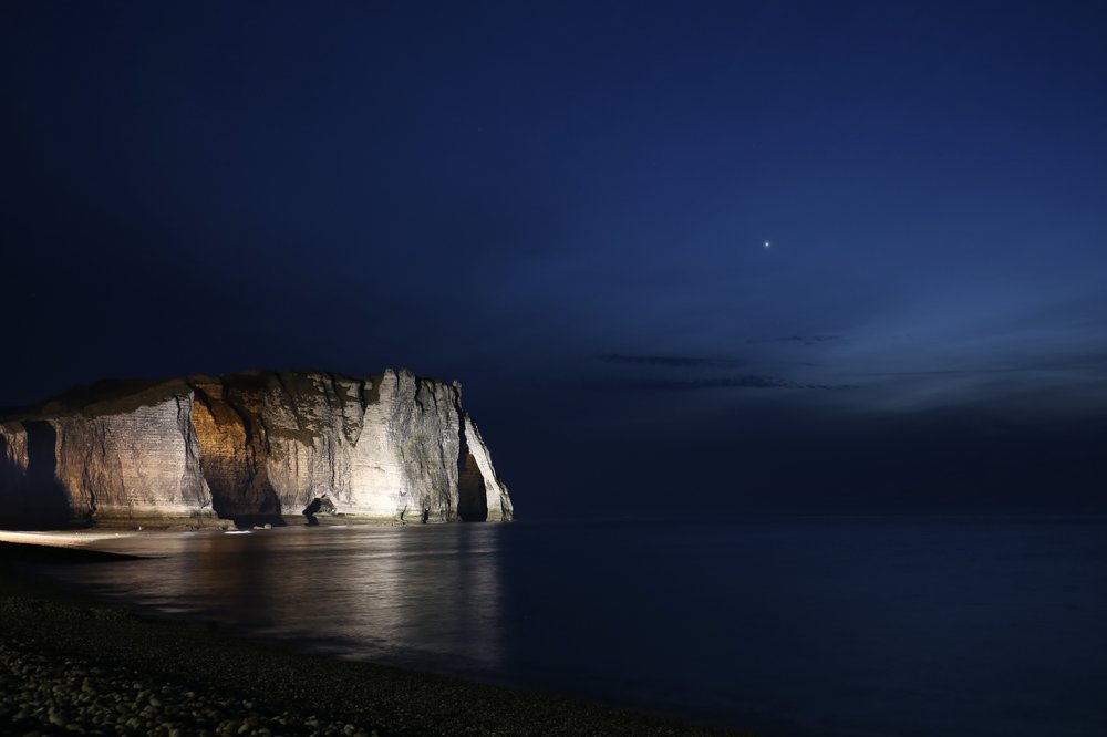 The cliffs of Etretat are lit up at night - shown here with a calm seashore and one bright star.