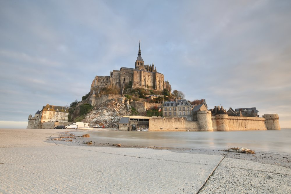 Mont Saint-Michel at high tide at sunrise - the beautiful medieval church on the island illuminated.