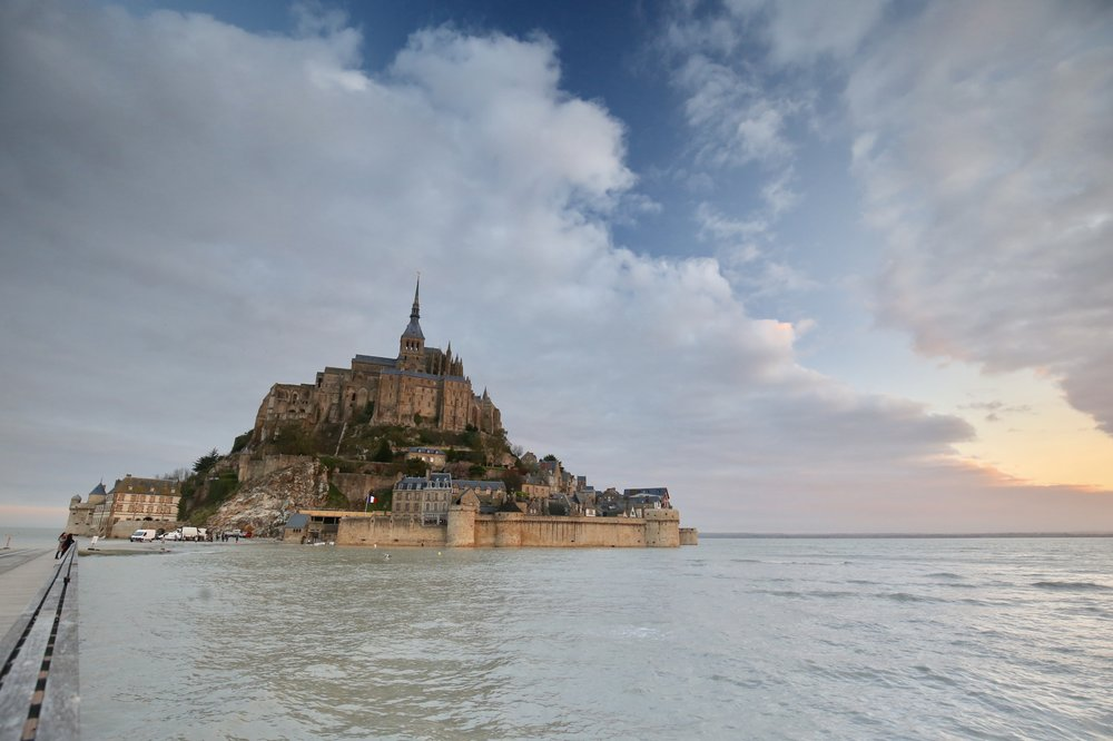 Mont Saint Michel at sunrise - with the sea lapping the walls at high tide.