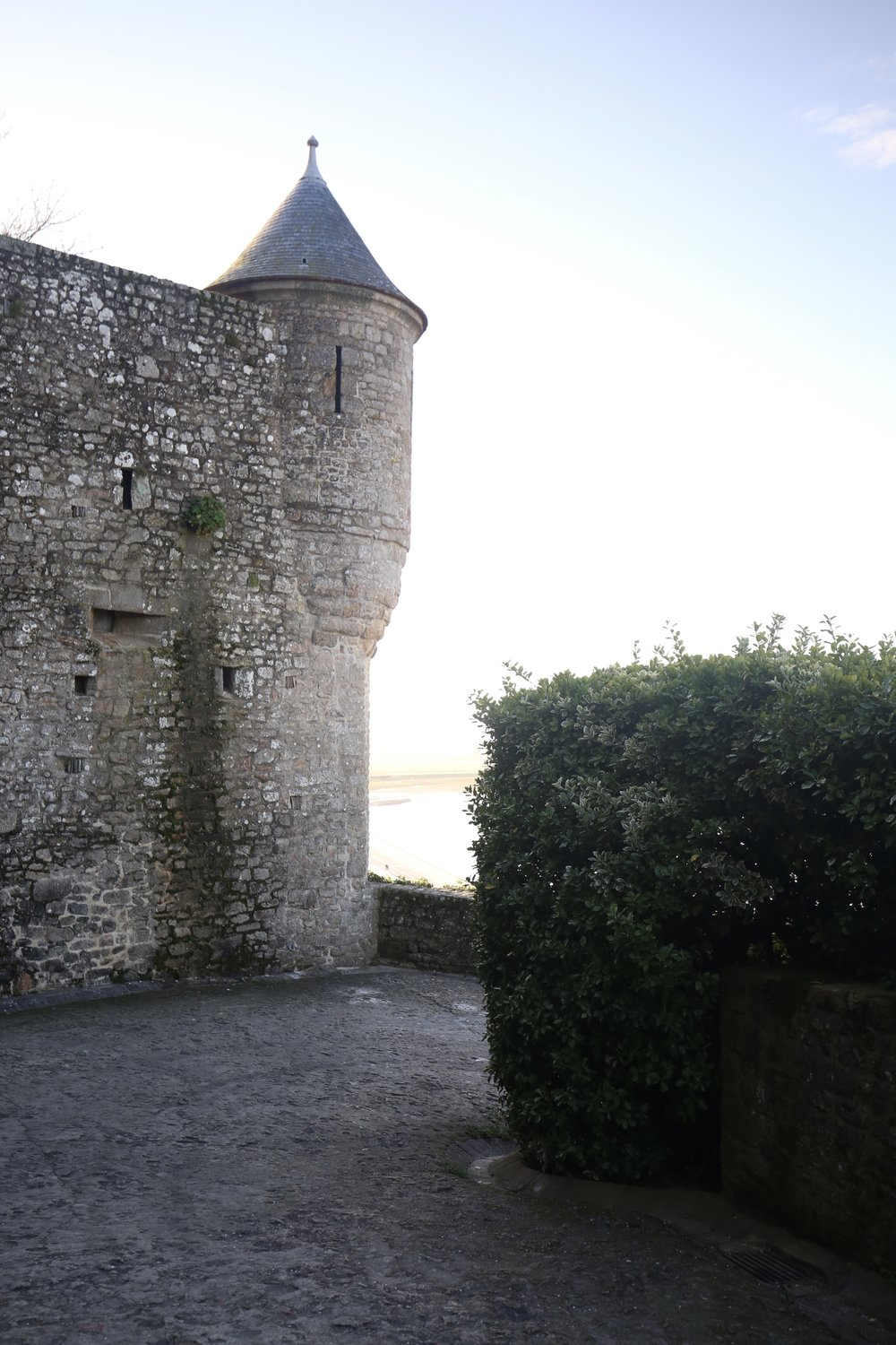 Stone castle turrets and hedges on the medieval island of Mont St Michel