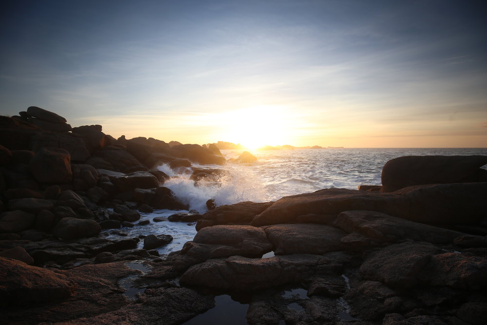 Sunset over the rocky seashore and Rose Coast of France.