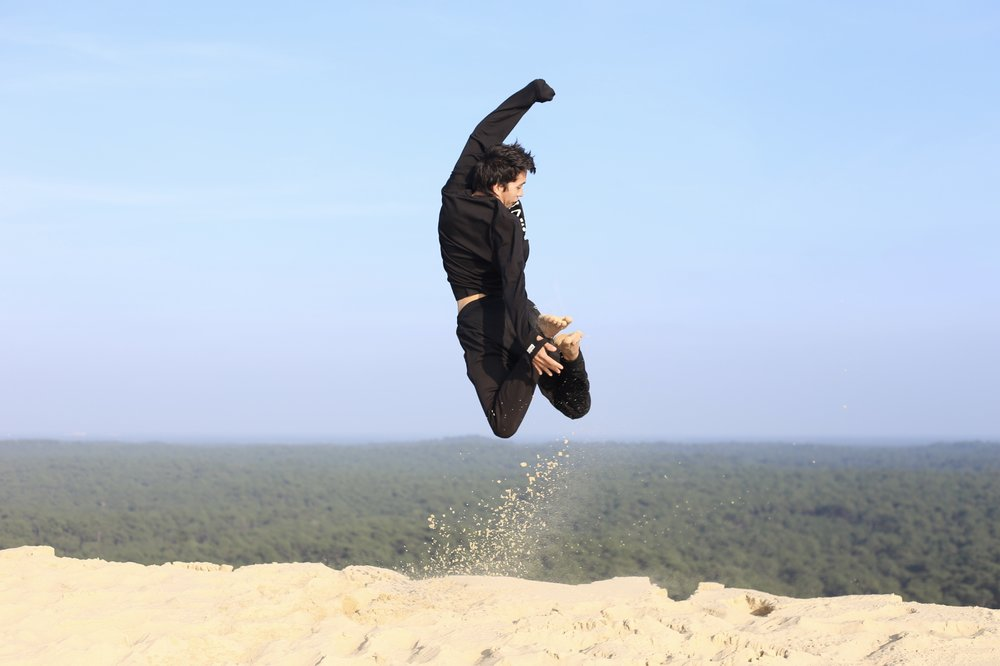 Oliver jumping off the edge of the giant sand Dune du Pilat.