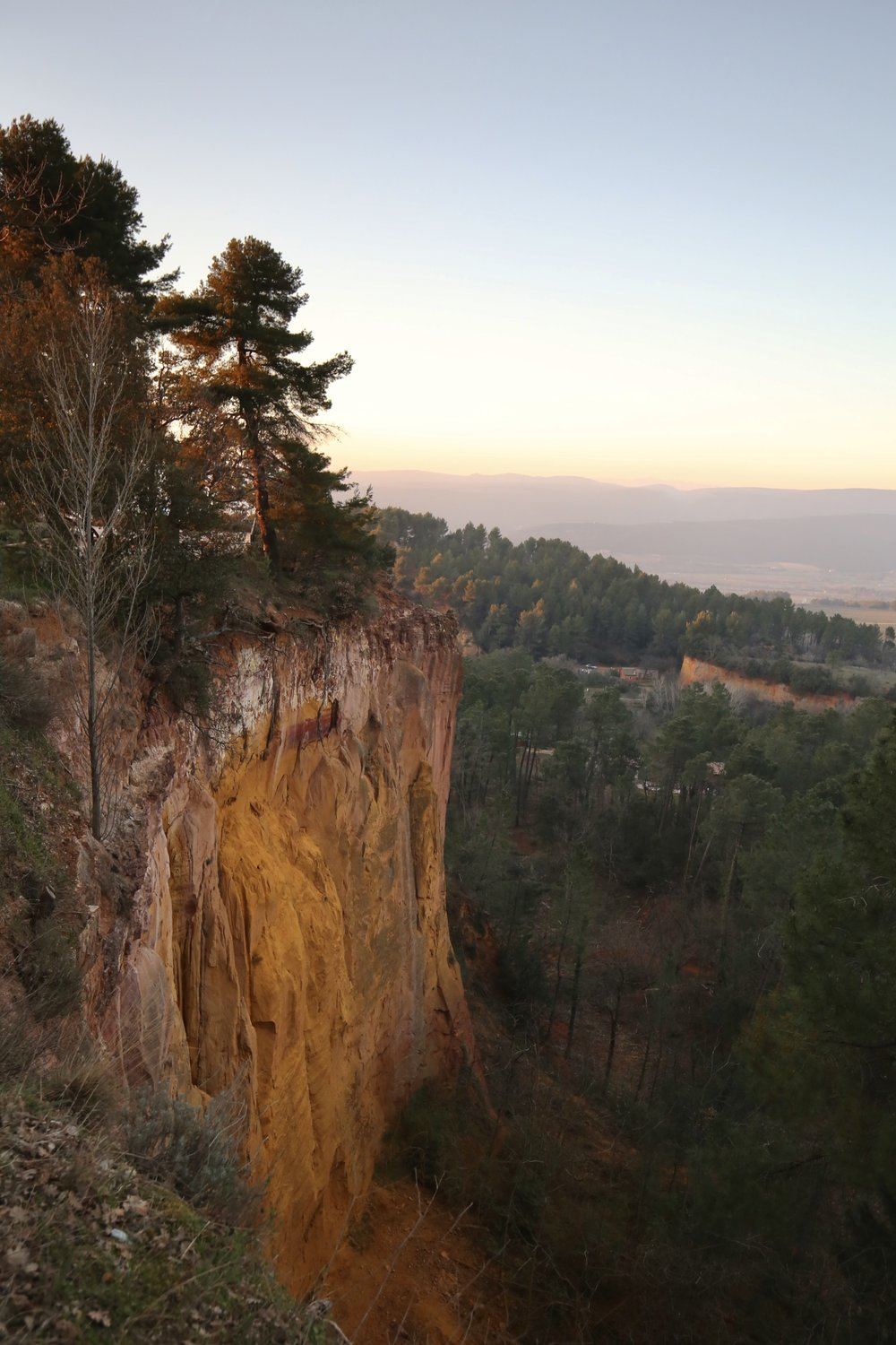 The ochre cliffs of Roussillon, France, at sunset.
